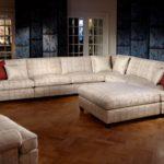 Stylowa, sofa wieloosobowa, z jasną tapicerką i czerwonymi detalami. Duresta, Colonial.