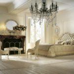 Elegancki fotel, łoże, lampa, lustro owalne, kominek, lampki nocne, stolik
