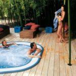 Sienna Professional 257x219x98 H basen Jacuzzi z rynną przelewową, zagłębiony w tarasie drewnianym.